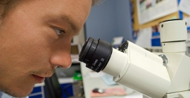 student looking through a microscope